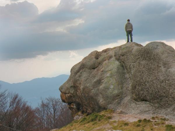 In der Natur zur Ruhe kommen. Felsen mit Mensch in der Landschaft